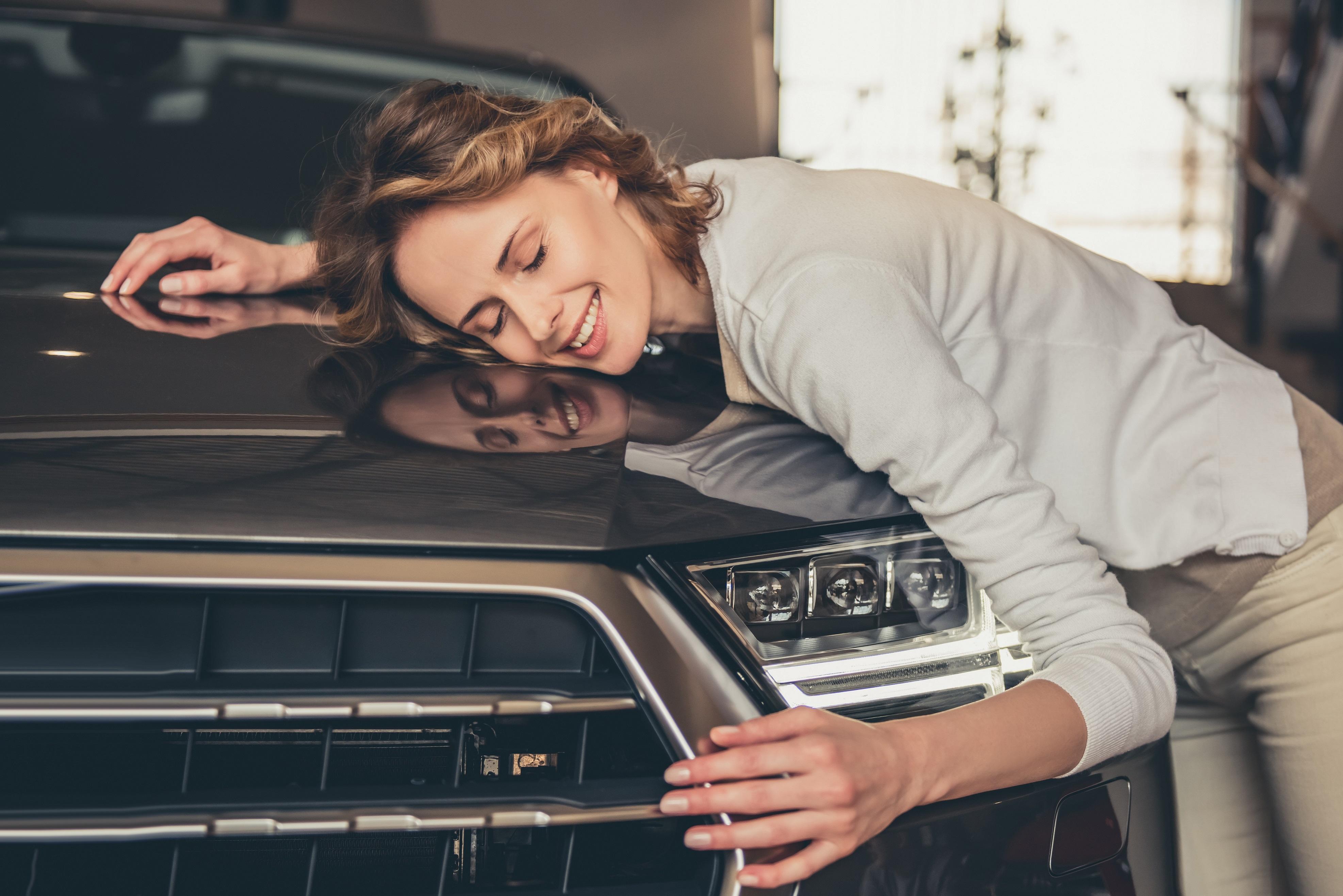 Young woman hugging car