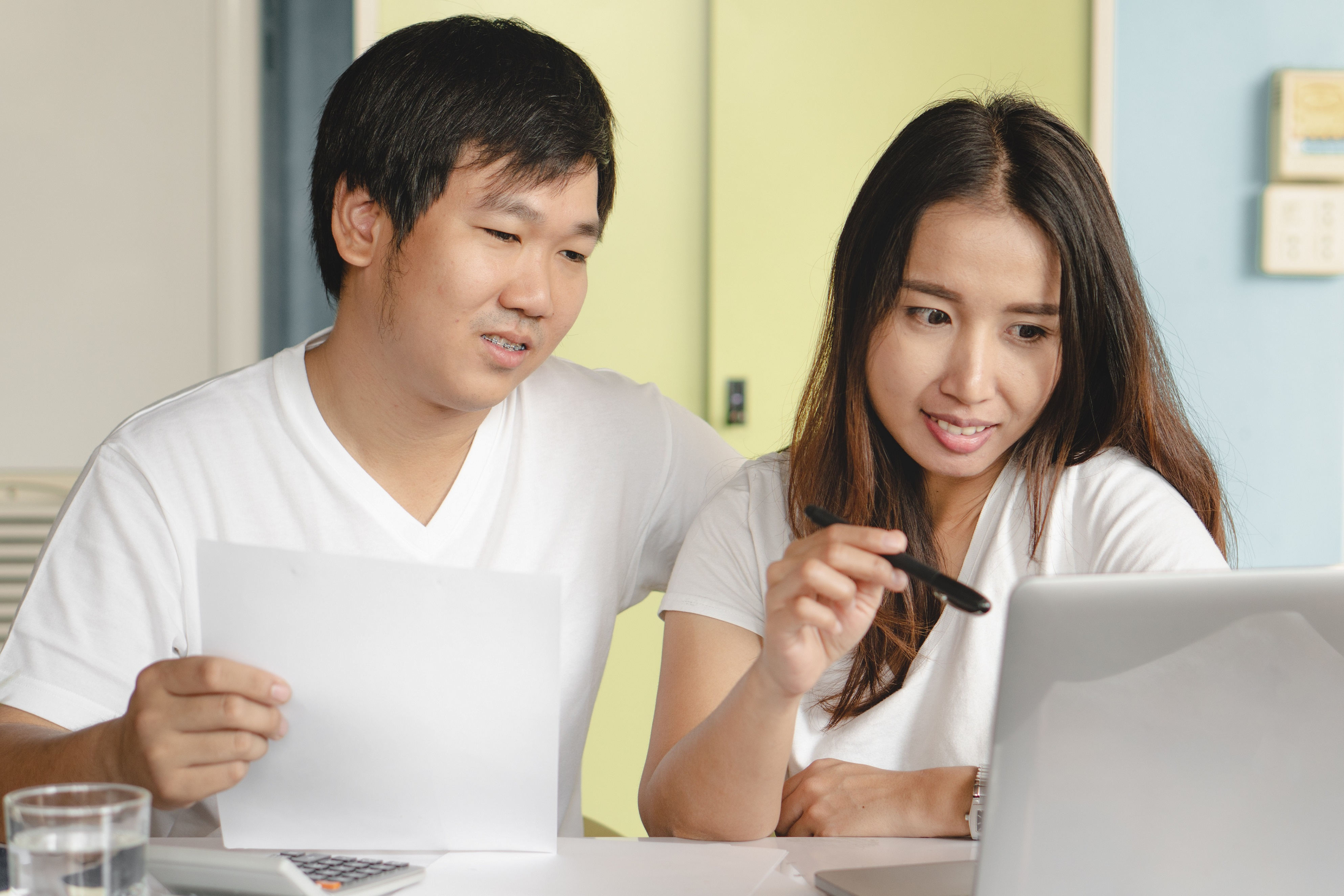 Young Asian couple doing finances on computer