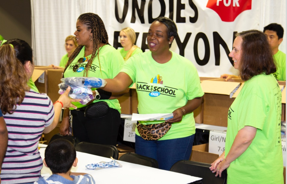 Santander Consumer employees hand out supplies to students at a Back to School event