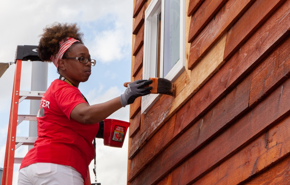 An african american woman in a red volunteer shirt paints a house they are building for veterans