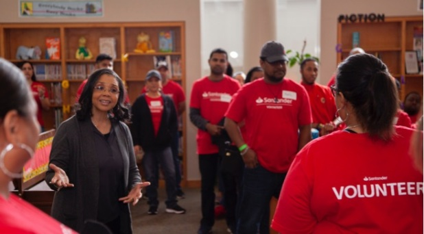 African american woman talking to a diverse group of Santander Consumer employees in red volunteer shirts