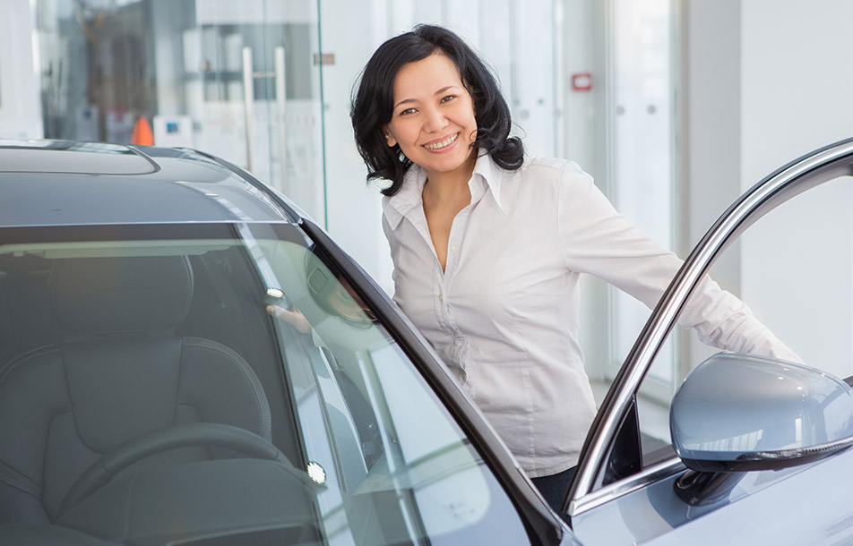 Smiling asian woman is buying a car at a dealership