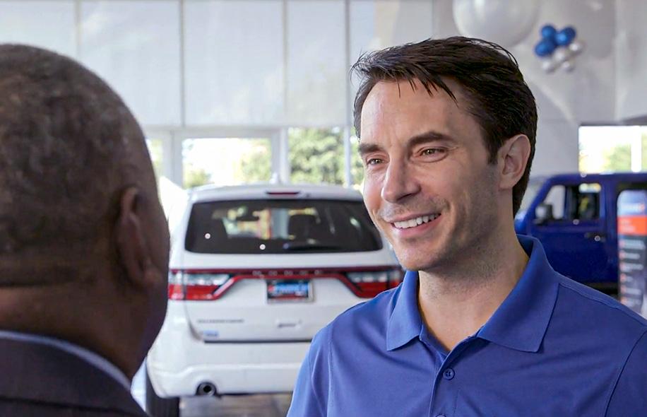 Smiling dealer talking to a Santander Consumer sales rep