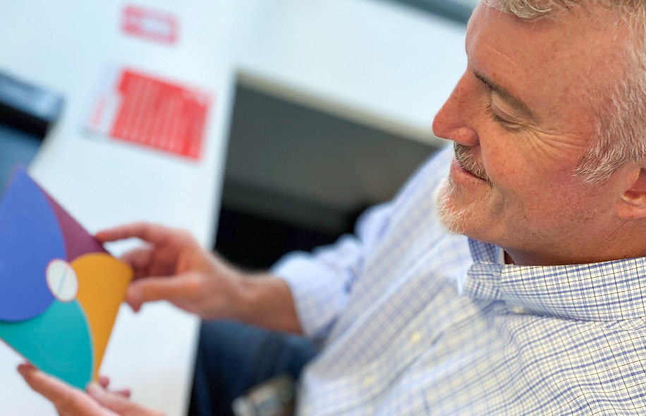 Smiling man with a grey goatee looking at a mulitcolored envelope