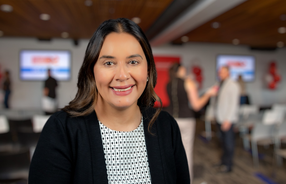 Sandra Rosa, Chief Human Resources Officer, standing in front of a Santander event