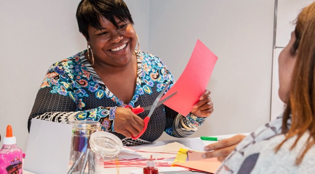 A smiling african american woman is working on a craft project