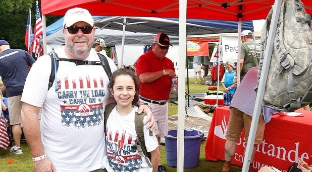 A man is standing with a child at a veterans event, both are wearing a Santander carry the load shirt.